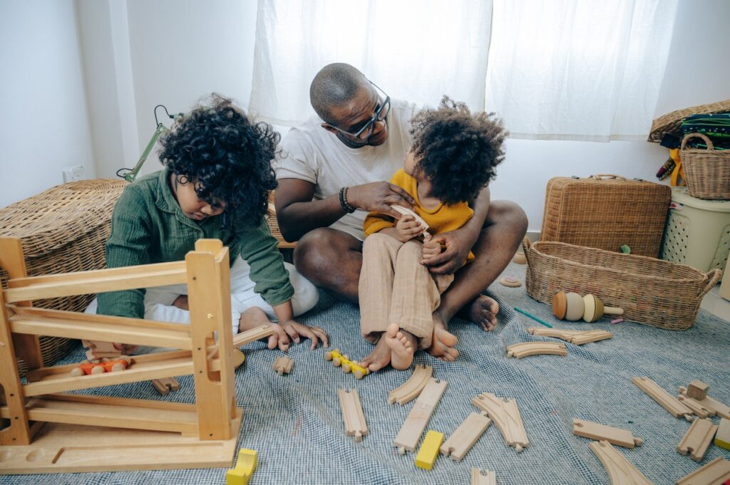 Dad playing with a train set with his children